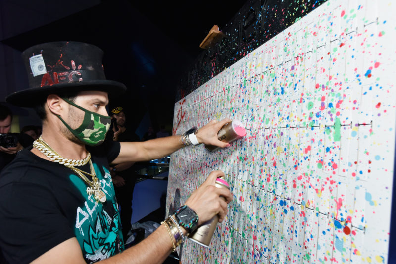 MIAMI, FL - DECEMBER 06:  Artist Alec Monopoly customizes his special design onstage at Art Basel Miami Beach pre-show with TAG Heuer Art Provocateur Alec Monopoly at Miami Design District on December 6, 2017 in Miami, Florida.  (Photo by Eugene Gologursky/Getty Images for TAG Heuer)